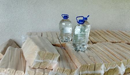 holzbriketts: Holzbriketts mit drei Flaschen Wasser