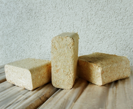 holzbriketts: Holzbriketts an der Wand des Hauses