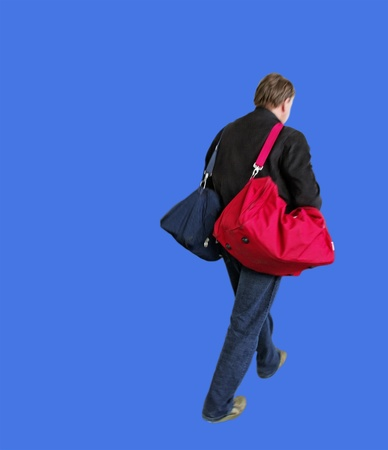 Hurry man with two bags, isolated on blue surface  photo