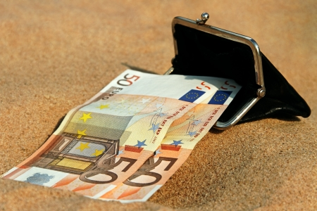 Big euro banknotes and small black purse on sand  photo