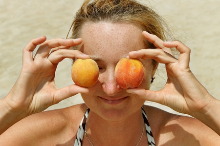 Freckled young woman with peach. photo