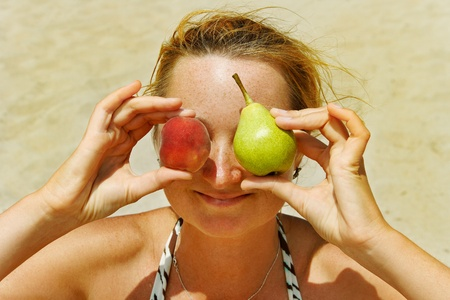 Freckled young woman with peach and pear. photo