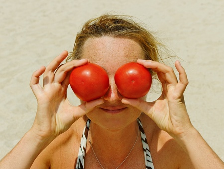Freckled young woman with two tomatoes. photo