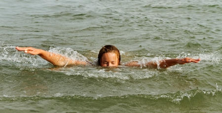Young woman is swimming in the sea. photo