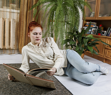Woman is sitting on the floor and reading a book. photo