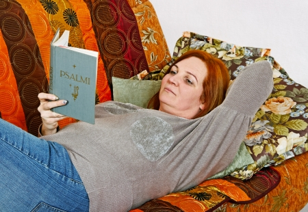 Adult woman is reading holly book.