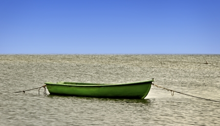 green boat: Green boat on the sea surface with bird. Stock Photo