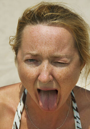 Woman showing her tongue. She was eating sour lemon. photo