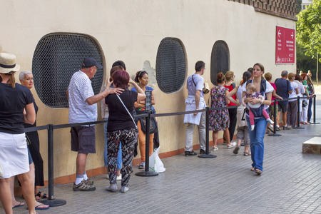 gothic build: BARCELONA, SPAIN-SEPTEMBER 18: Long queue of people for ticket to La Sagrada Familia - the impressive cathedral designed by Gaudi, which is being build since 19 March 1882 and is not finished yet September 18, 2014 in Barcelona, Spain.