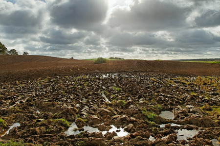 ploblem: Plowed field with small tractor on the hill. Stock Photo