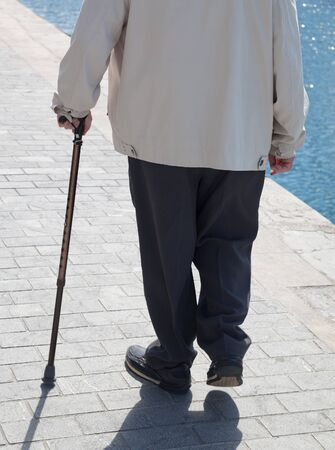 people walking white background: Old man with crutch is walking on the promenade.
