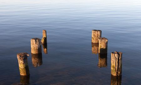 decrepit: Decrepit pillars of old pier at the coastline.