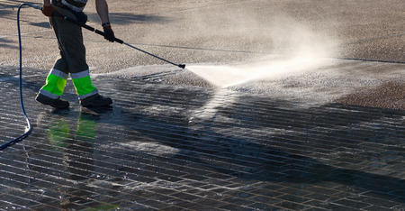 pressurized: Wet cleaning of street with pressurized water.