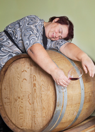 fermenting: Woman drinking wine next to the barrel. Stock Photo