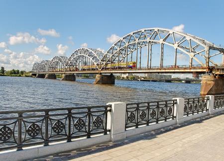 Railway bridge with two trains across river Daugava in Riga. Stock Photo