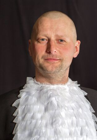 skinhead: Skinhead man in a jabot on black background. Stock Photo