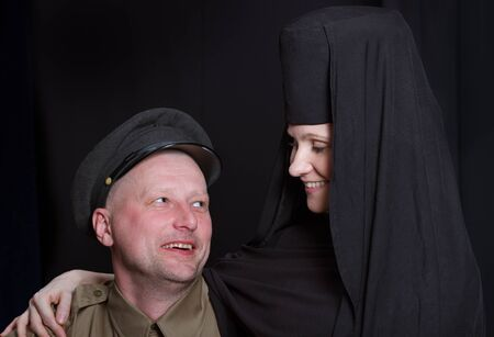 militaire sexy: Femme dans une robe de moine et soldat sur un fond noir. Banque d'images