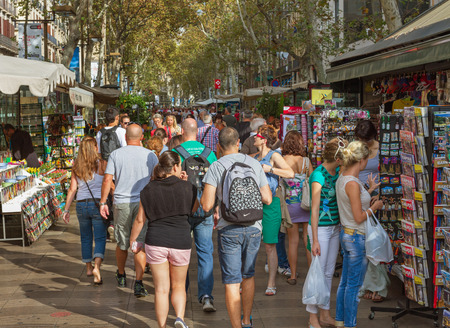 BARCELONA, SPAIN - SEPTEMBER 18, 2014: Barcelona is the capital city of the autonomous community of Catalonia in Spain and Spains second most populated city. Crowd of people at la Rambla in Barcelona, Spain. Editorial