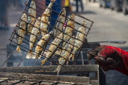 Fried fish on a hot coal on the banks of the river Dora in Portugal. Stock Photo