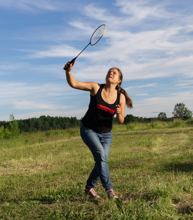 shuttlecock: Young woman playing badminton with partner on a field in countryside.