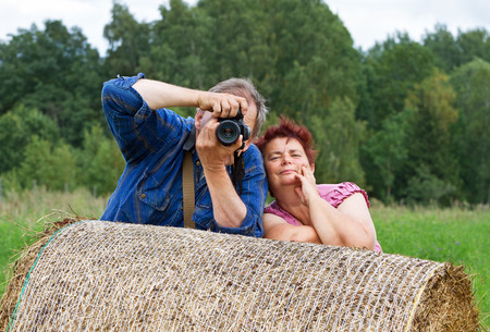 Photographer in countryside with women. Stock Photo