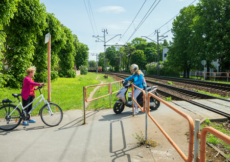 LATVIA, JURMALA - JUNE 6: Two women are crossing a railway on the crosswalk after train is passing on 4 June 2017, Jurmala, Latvia.