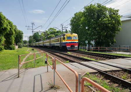 LATVIA, JURMALA - JUNE 6: Electrified train on a railway through Jurmala is next to the crosswalk on 4 June 2017, Jurmala, Latvia.