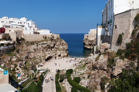 ITALY, POLIGNANO A MARE - OCTOBER 3: Polignano a Mare is a town located on the Adriatic Sea. People bathing in the Mediterranean sea at the city beach on 3 October 2017, Polignano a Mare, Italy.