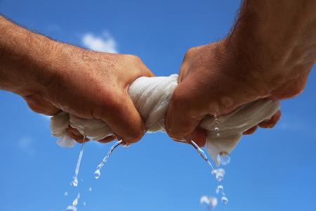 L'uomo strizza lo straccio bagnato.