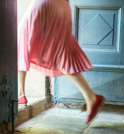 Woman in pink steps over the threshold of an old house.