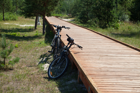 LATVIA, JURMALA - JULY 25: Bike tourism is the smartest way to discover this world of ours. Two bicycles at the wooden path in dunes of Baltic sea on 25 July 2018, Jurmala, Latvia.