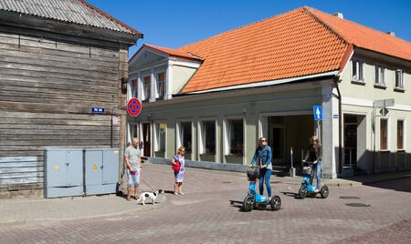 VENSPILS,  LATVIA - 31 July: City is situated on the Venta River and the Baltic Sea, and has an ice-free port. Two young women is riding by gyro scooters on the old town street on 31 July 2016, Ventspils, Latvia. Stockfoto