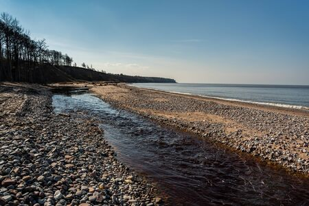 Natural landscape of small river flowing to the Baltic sea. Фото со стока