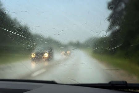 View to road through car window in rainy day.