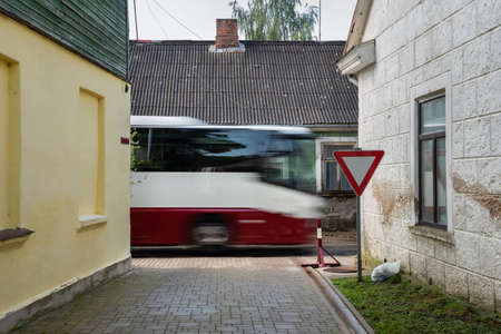 Big bus on narrow street of a small city.