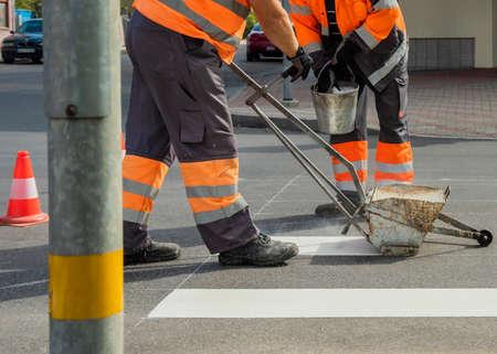 Men works on the road, painting white lines of crosswalk. Reklamní fotografie