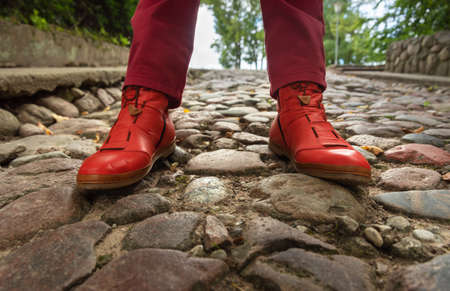 Legs in red boots on a old cobbled road. Reklamní fotografie