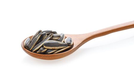Sunflower seed on a wooden spoon on white background. Foto de archivo