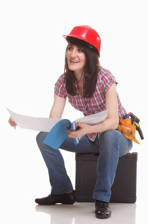Woman in a helmet sits and reads documents  Isolated on white photo