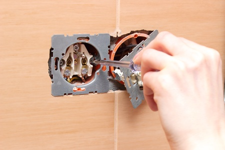 Hand of an electrician installing a power socket photo