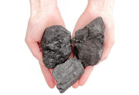 anthracite coal: Woman s hand with coal lump isolated on white background