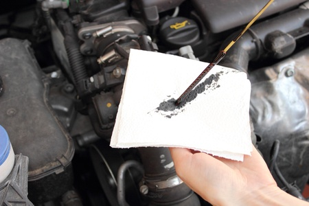 Auto mechanic checks the oil level in a car engine photo