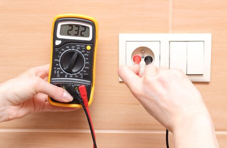 Hand electrician with multimeter checking voltage photo