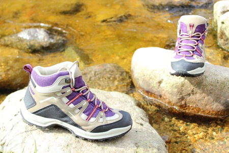 Pair of hiking boots over a mountain stream photo