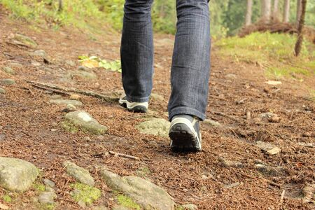 Legs of a woman in boots hiking on the mountain path photo