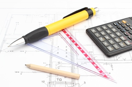 Drawing accessories and calculator on construction drawing of house photo