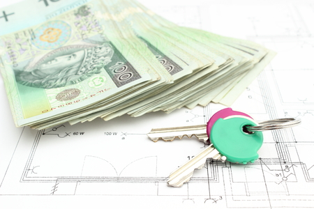 Stack of money with key lying on construction drawing of house photo