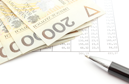 Closeup of polish banknotes and ballpen on spreadsheet photo