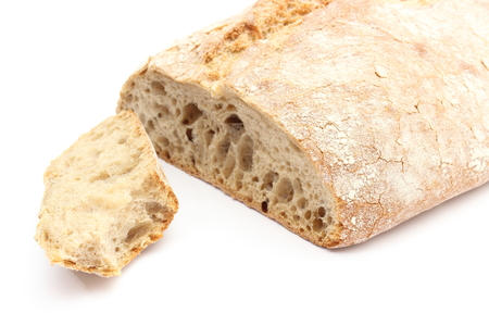 Closeup of bitten slice of rye bread and loaf bread  isolated on white background photo