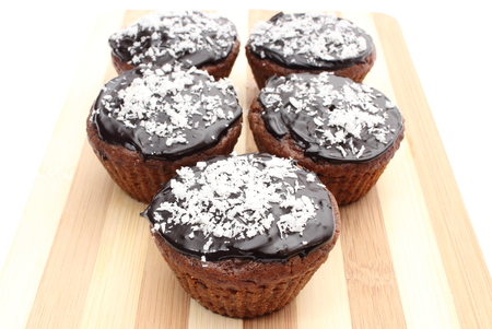 desiccated: Closeup of fresh baked muffin with cacao, chocolate and desiccated coconut on chopping board  Isolated on white background Stock Photo